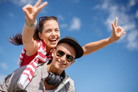 pareja adolescente: vacaciones de verano, las relaciones y el concepto de adolescencia - adolescentes sonrientes en las gafas de sol que se divierten fuera y que muestran la v-muestra