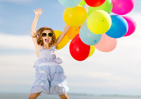 summer holidays, celebration, children and people concept - happy jumping girl with colorful balloons outdoors Foto de archivo