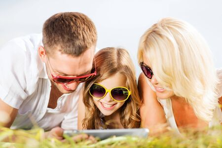 summer holidays, children and people concept - happy family with tablet pc, blue sky and green grass taking picture photo