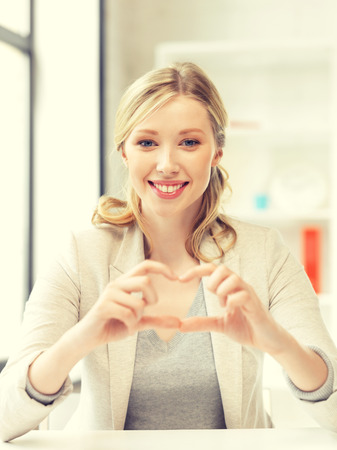 one of a kind: bright picture of young woman showing heart sign