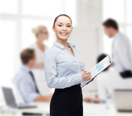 office notes: business and education concept - friendly young smiling businesswoman with clipboard and pen