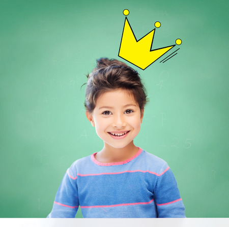 education, school and children concept - little student girl over green chalk board background and crown doodle Stock Photo