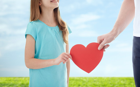 people, love, charity and family concept - close up of girl and male hand holding red heart shape over blue sky and grass background photo