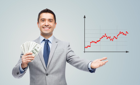 growing success: business, people, success and finances concept - smiling businessman with american dollar money and growing chart over gray background