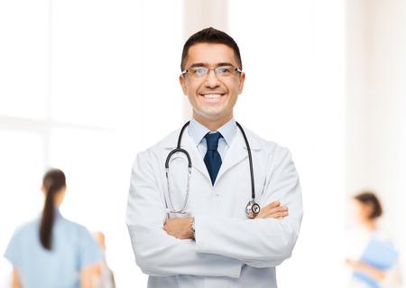 gezondheidszorg, beroep, mensen en geneeskunde concept - lachende mannelijke arts in witte jas over groep van artsen in het ziekenhuis achtergrond Stockfoto