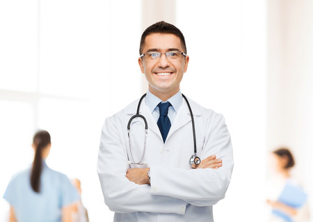 healthcare: healthcare, profession, people and medicine concept - smiling male doctor in white coat over group of medics at hospital background