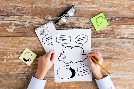 business, education and people concept - close up of female hands drawing text bubbles on paper sheet with pencil, stickers and eyeglasses at table