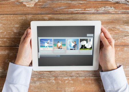 tablet pc in hand: people, multimedia and technology concept - close up of hands with video gallery slideshow on tablet pc at table Stock Photo