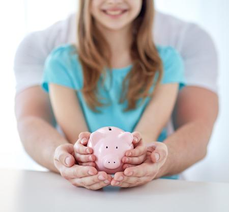 家族、子供、お金、投資、人々 の概念 - は父と娘の両手貯金箱ピンクのクローズ アップ