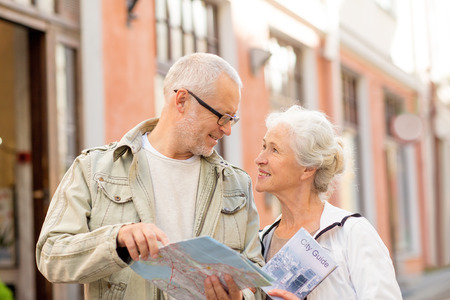 retirement happy man: family, age, tourism, travel and people concept - senior couple with map and city guide on street