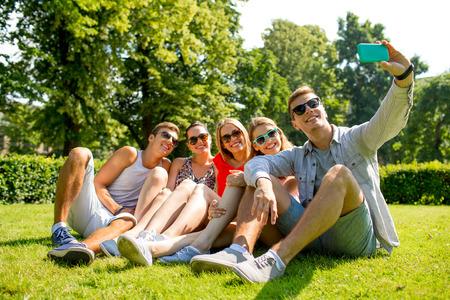 amicizia: amicizia, il tempo libero, l'estate, la tecnologia e la gente il concetto - gruppo di amici sorridenti con lo smartphone seduti sull'erba e fare selfie nel parco