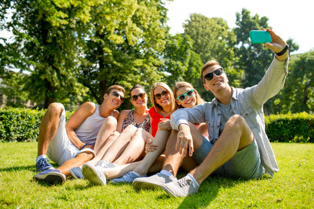 friendship: friendship, leisure, summer, technology and people concept - group of smiling friends with smartphone sitting on grass and making selfie in park