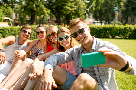 group picture: friendship, leisure, summer, technology and people concept - group of smiling friends with smartphone sitting on grass and making selfie in park