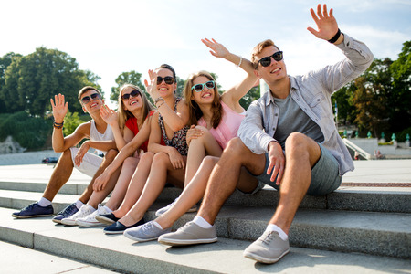 friendship: friendship, leisure, summer, gesture and people concept - group of smiling friends sitting on city street and waving hands