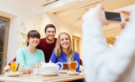 people, leisure, friendship and technology concept - group of happy friends with smartphone taking picture and drinking tea at cafe photo