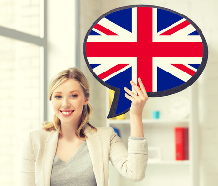 british english: education, fogeign language, english, people and communication concept - smiling woman holding text bubble of british flag