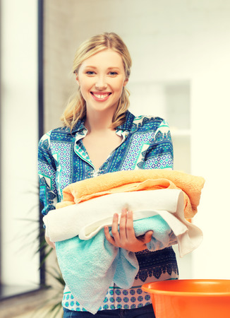 bright picture of lovely housewife with towels. photo