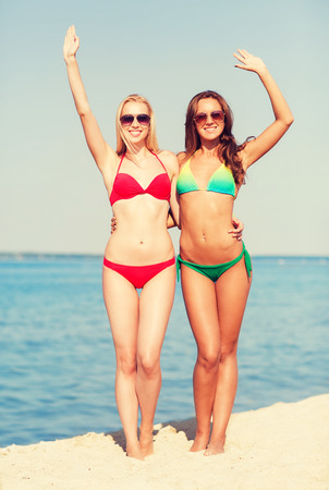 summer vacation, holidays, travel, gesture and people concept - two smiling young women waving hands on beach Reklamní fotografie