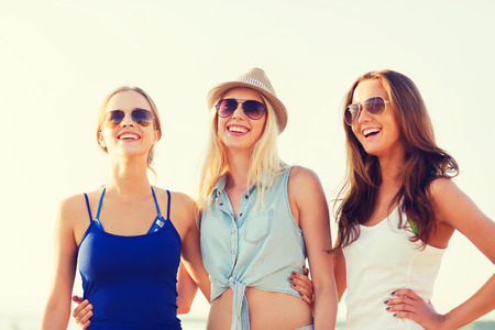 bachelorette: summer vacation, holidays, travel and people concept - group of smiling young women in sunglasses and casual clothes on beach