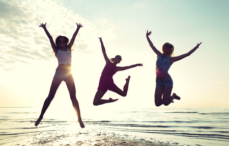 friendship, summer vacation, freedom, happiness and people concept - group of happy female friends dancing and jumping on beach Foto de archivo