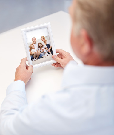 old photograph: oldness, memories, nostalgia and people concept - close up of old man holding and looking at happy family photo Stock Photo