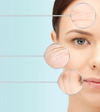 arrugas: belleza, el envejecimiento, las personas, cuidado de la piel y el concepto de salud - cara hermosa mujer joven con arrugas sobre fondo azul Foto de archivo