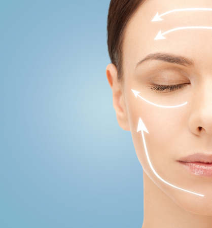 surgeries: beauty, people, skincare and plastic surgery concept - beautiful young woman face with facelift marks over blue background