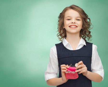 putting money in pocket: finances, childhood, people, money and savings concept - happy little girl with purse and euro coin over over green chalk board background