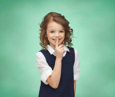 shush: people, children, secrecy and mystery concept - happy girl showing hush gesture over green chalk board background Stock Photo