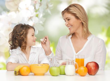 yogurt natural: personas, estilo de vida saludable, la familia y el concepto de alimentos - feliz madre e hija que comen desayuno saludable sobre fondo del jardín verde del verano