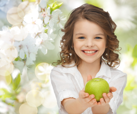 pretty preteen: people, children, healthy eating, ecology and food concept- happy girl holding green apple over summer or spring garden background Stock Photo