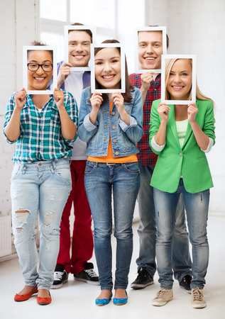 pretense: friends, people, hypocrisy and pretense concept - group of happy friends or students covering faces with own photos