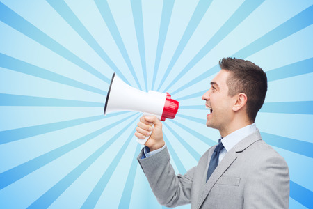 successful campaign: business, people and public announcement concept - happy businessman in suit speaking to megaphone over blue burst rays background