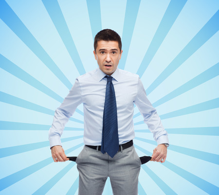 empty pockets: business, people, bankruptcy and failure concept - surprised businessman showing empty pockets over blue burst rays background