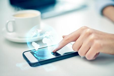 Affaires, technologie, communication, loisirs et gens concept - close up de la femme la main avec smartphone et globe hologramme Banque d'images - 38943077