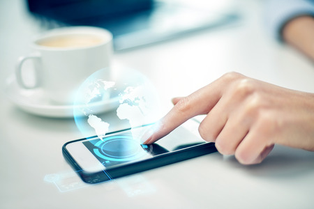 business, technology, communication, leisure and people concept - close up of woman hand with smartphone and globe hologram