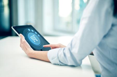 business, technologie, online winkelen en mensen concept - close-up van vrouw met tablet pc computer op kantoor of thuis