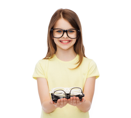 people and vision concept - smiling cute little girl in black eyeglasses holding many glasses in her hands Stock Photo