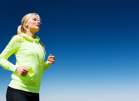 sport and lifestyle concept - woman doing running outdoors