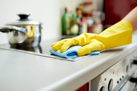 cookers: people, housework and housekeeping concept - close up of woman hand in protective glove with rag cleaning cooker at home kitchen