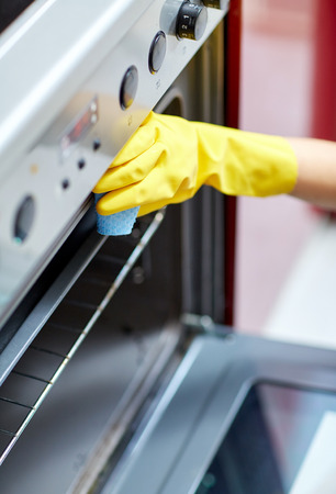 housecleaning: people, housework and housekeeping concept - close up of woman hand in protective glove with rag cleaning oven at home kitchen