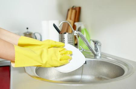 lavar trastes: las personas, las tareas domésticas, lavar los platos y la limpieza concepto - cerca de la mujer de las manos en guantes de protección que lavan platos con una esponja en la cocina de casa Foto de archivo