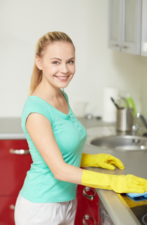 housewife gloves: people, housework and housekeeping concept - happy woman cleaning cooker at home kitchen