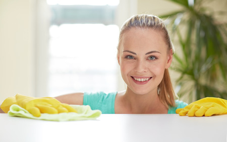 maid: people, housework and housekeeping concept - happy woman cleaning table at home kitchen