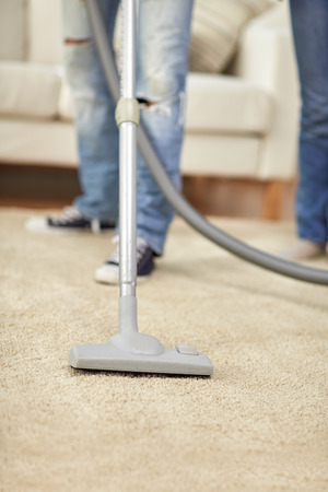 hoover: people, housework and housekeeping concept - close up of human legs and vacuum cleaner on carpet at home Stock Photo