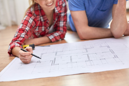 home improvements: repair, building, renovation and people concept - close up of happy couple looking at blueprint at home