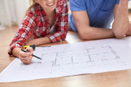 pareja en casa: reparación, construcción, renovación y concepto de la gente - cerca de la pareja feliz que mira el modelo en casa Foto de archivo