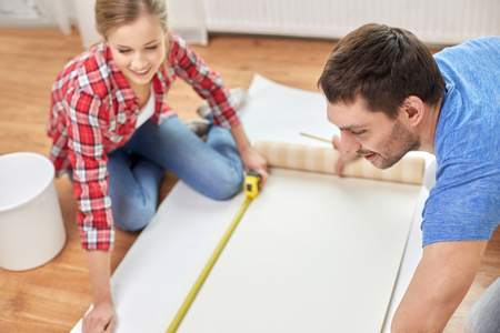 repair, building and people concept - close up of couple with ruler measuring wallpaper at home photo