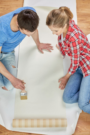 smearing: repair, renovation, building and people concept - close up of couple smearing wallpaper with glue on floor at home
