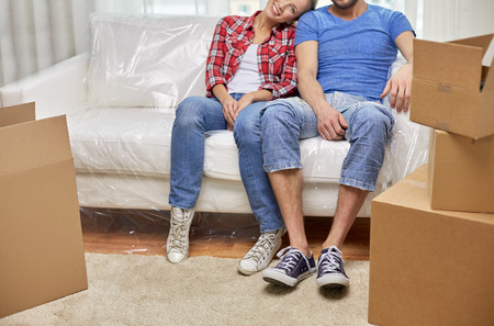 first move: moving, home, repair and people concept - close up of couple legs relaxing and sitting on sofa in new apartment